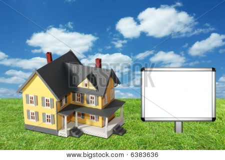 Model house on green grass with blank sign
