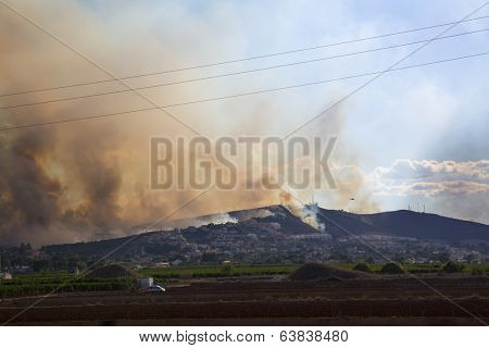 CUMBRES DE CALICANTO, TORRENT, VALENCIA, SPAIN - April 22, 2014: Fire burning mountain forest and village, hundred of arson people in Torrent, Cumbres de Calicanto, Valencia, Spain - April 22, 2014