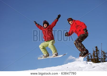Two snowboarder jumping on the background of blue sky