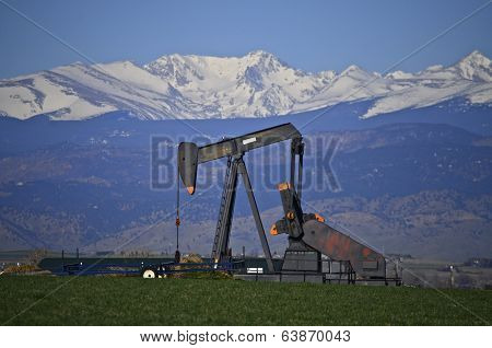 Landscape view of a pump jack , oil well in front of the snow capped Rocky Mountain poster