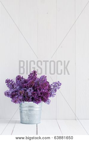 Bouquet of beautiful spring flowers of lilac in a vase on a white vintage wooden board home decor in a rustic style poster