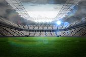 Large football stadium with lights under cloudy sky poster