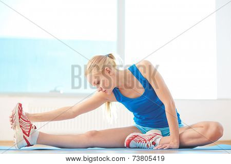 Sporty woman in activewear doing stretching exercise in gym