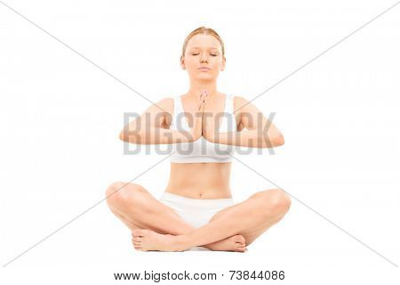 Young woman meditating seated on the floor isolated on white background