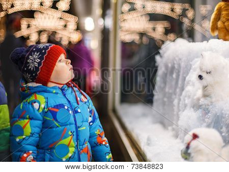 Adorable Little Boy Looking Through The Window At Christmas Decoration In The Shop