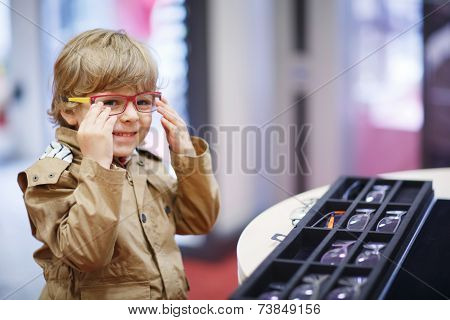 Cute Little Kid Boy At Optician Store During Choosing His New Glasses