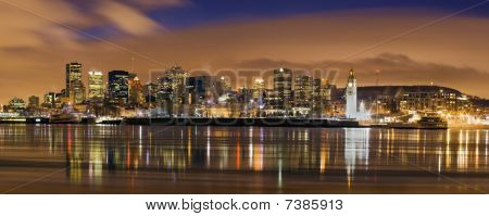 Downtown Skyline Panorama  At Dusk In Montreal Canada With River Reflection