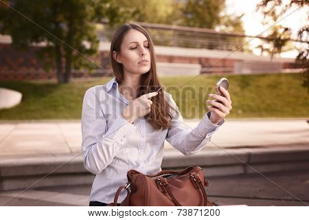 Young Woman Refreshing Her Hair In A Street