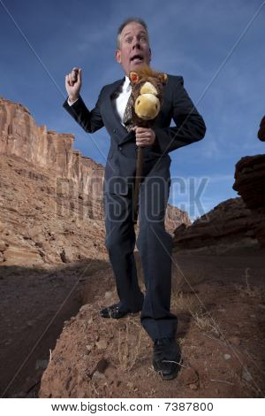 Businessman Riding A Stick Horse