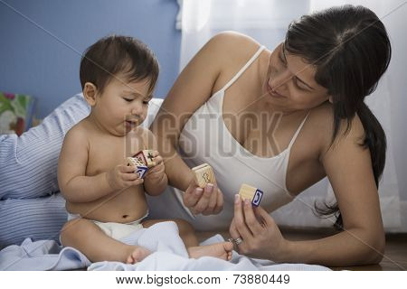 Hispanic mother and baby playing with blocks