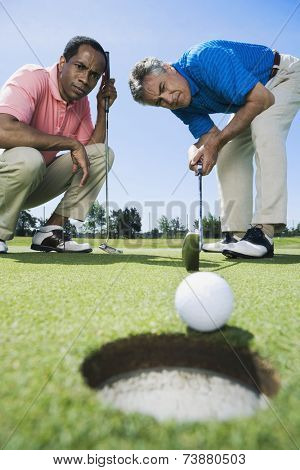 Multi-ethnic men looking at golf ball