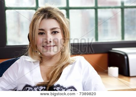 Smiling Businesswoman With Headset Sitting In Office