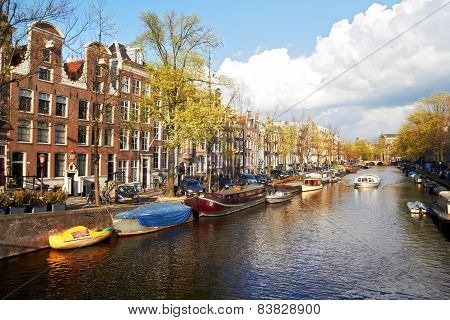 Amsterdam canal with trees and small boats