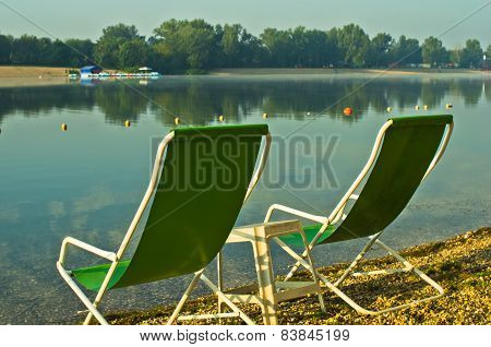 Two green chairs at the beach of Ada lake in Belgrade