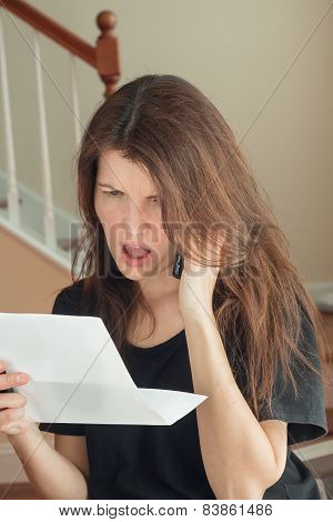 Upset Woman Holding A Bill And Talking On The Phone