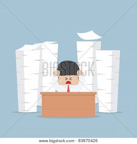 Tired And Busy Businessman With Piles Of Work To Do