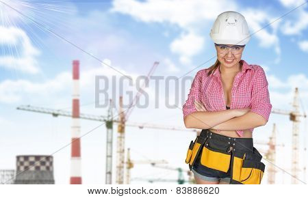 Woman in tool belt and helmet. Tower cranes, chimneys as backdrop