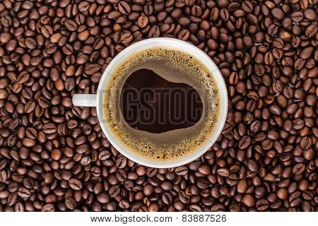 white cup of coffee on a heap of roasted coffee beans