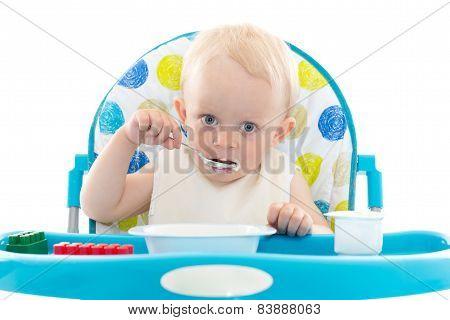 Sweet Baby With Spoon Eats The Yogurt.