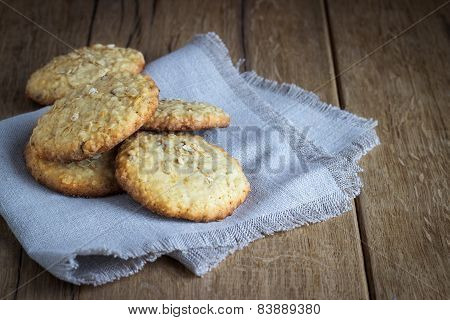 oatmeal cookies on white linen napkin on wooden table.