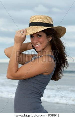 Young Brunette Woman in Straw Hat at the Beach