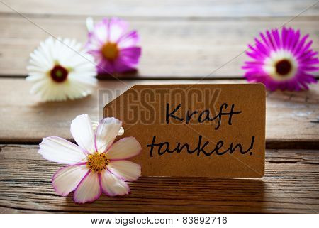 Label With German Text Kraft Tanken Means Recarge Batteries With Cosmea Blossoms