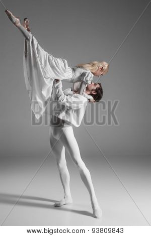 Two young classic ballet dancers practicing. attractive dancing performers  in white suits over gray background poster