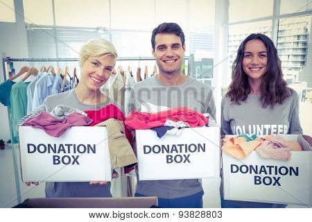 Happy volunteers friends holding donation boxes