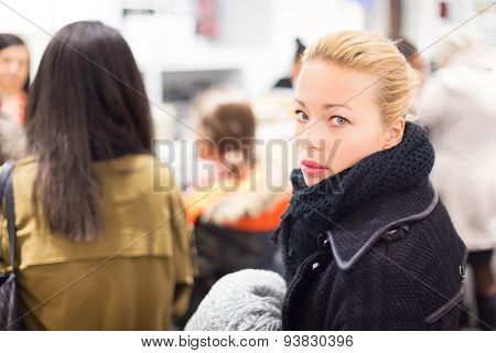 Female shopper queuing in line at cashier.