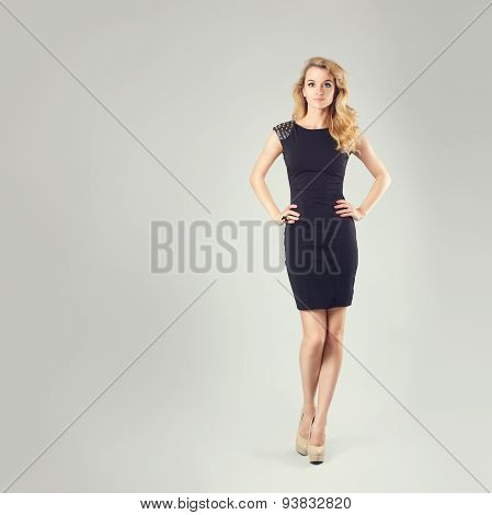 Beautiful Woman in Black Dress with Hands on Hips