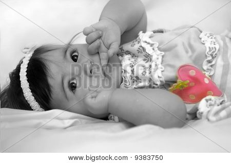 baby girl with finger in her mouth and pink strawberry accentuated