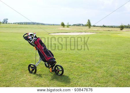 Golf club bag on pushcart at golf course against sky