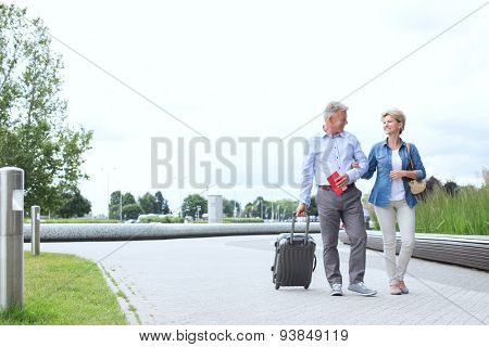 Middle-aged couple with luggage walking on footpath against clear sky