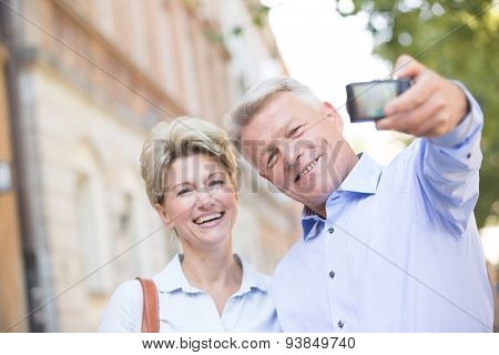 Cheerful middle-aged couple taking self portrait outdoors