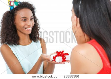 Nice girl presenting the box to friend.