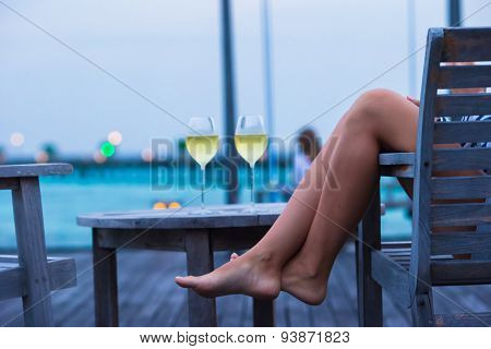 Young girl with white wine at evening outdoor cafe