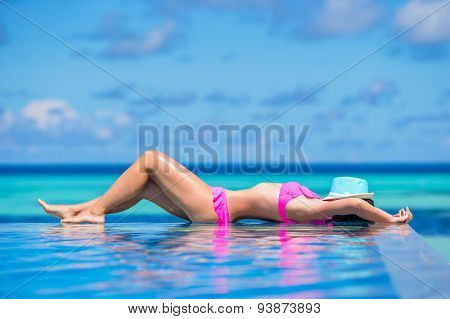 Young beautiful woman enjoying summer vacation in luxury swimming pool