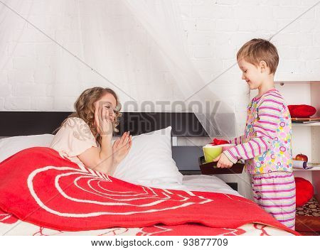 Little son giving a tray with breakfast to his mom