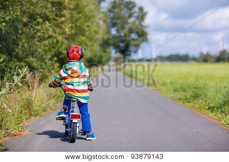 Kid Boy In Helmet Riding His First Bike, Outdoors