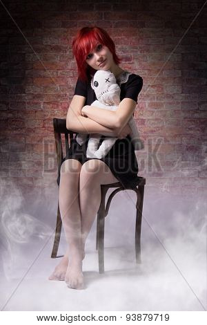 Girl With A Doll On Chair In The Fog