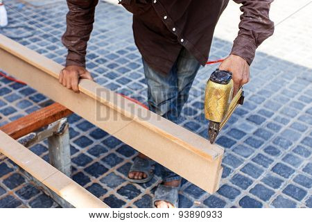 Hand Holding Nail Gun To Fix The Wood