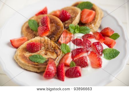 Pancakes with yogurt, fresh strawberries and mint