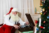 Santa Claus sitting in comfortable chair near retro turntable at home poster