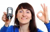 Smiling woman holding glucose meter measuring sugar level concept for diabetes. Isolated on white background poster