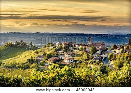 view of Treiso village in langhe northern italy on late summer day at twilight