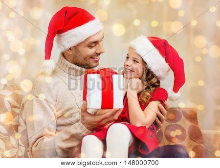 family, christmas, x-mas, winter, happiness and people concept - smiling father giving daughter gift box