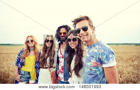 nature, summer, youth culture and people concept - smiling young hippie friends on cereal field