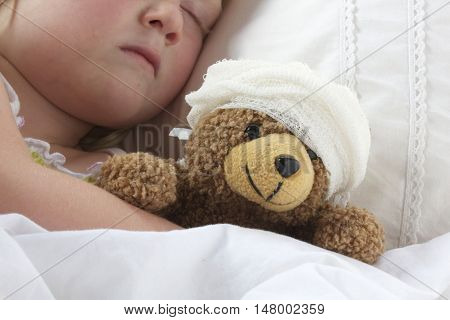 A young girl poorly in bad cuddling her teddy who also feels poorly.