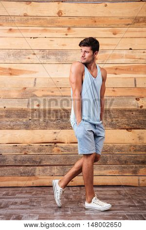 Full length portrait of a fitness man walking isolated on a wooden background