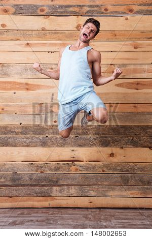 Happy excited cheerful young man jumping and celebrating success over wooden background